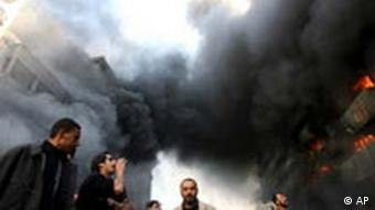 People gather in front of a burning building after a double car bomb attack in central Baghdad, Iraq, Monday, Feb. 12, 2007.