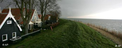 A row of houses atop a grass embankment, water at the bottom