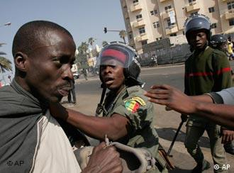 Senegalese police confront an opposition supporter in the Medina neighborhood of Dakar, Senegal, Saturday, Jan. 27, 2007. Riot police fired tear gas at protesters calling for early parliamentary elections Saturday, beating back the crowd with rifle butts and detaining the head of the country's main opposition party. (AP Photo/Rebecca Blackwell)