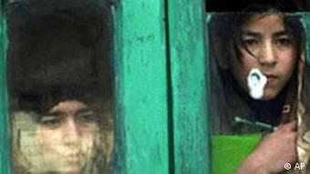 Kashmiri children watch through a window in Srinagar, where curfews and protests are common