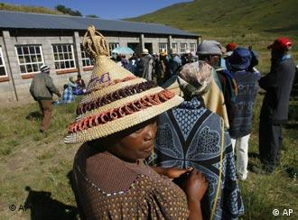 A Lesotho woman wearing a traditional hat lines up with others in the village of Likalaneng, 50 miles east of the capital