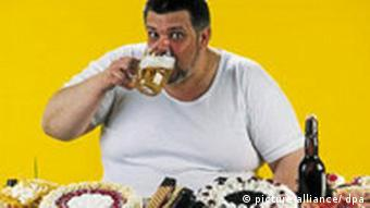 An overweight man with a table heaving with food and drink