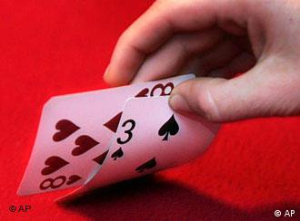 Hand holding cards in front of a red background