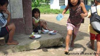 Vier Kinder sitzen und stehen um Teller mit Essen herum