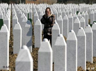 Bosnian Muslim man Huseinovic Hamdija says prayer near grave stones at the memorial center of Potocari, near Srebrenica,