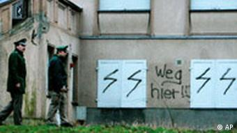 Two policemen walk past antisemitic signs painted on the back of a Jewish school and Kindergarden in Berlin