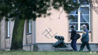 Two people walking past antisemitic signs painted on a Jewish school and kindergarten in Berlin