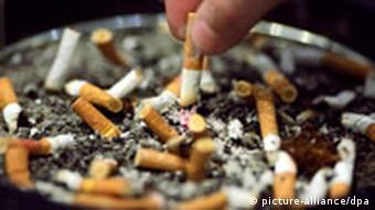 Fingers of a person stubbing out a cigarette in full ashtray