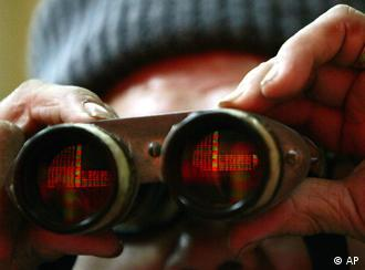 A Chinese man watches the screens of the Shanghai Stock Exchange through binoculars