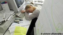 Bei dem gestellten Symbolbild zum Thema Büroschlaf sitzt eine junge Frau mit auf die Arme gelegtem Kopf vor einem Computer-Bildschirm in einem Büro (Illustration zum Thema Bürosschlaf, Müdigkeit bei der Arbeit - Foto vom 10.10.2004). Foto: Patrick Pleul +++(c) dpa - Report+++