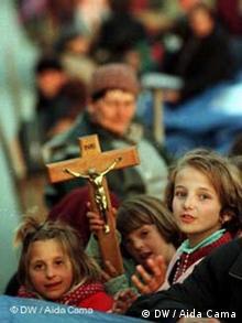 Albanische Christen aus dem Kosovo mit Kreuz
