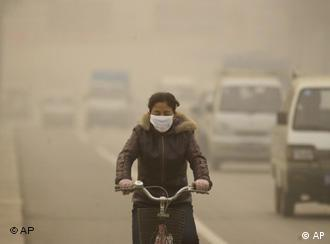 A woman covers her mouth while driving through the smog on bike