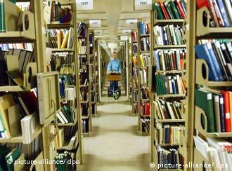 An employee at Munich's Bavarian State Library pushes a book cart between shelves of books