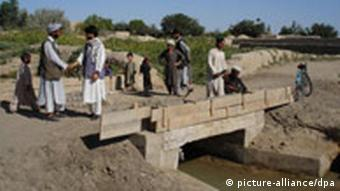 Afghans stand on a bridge