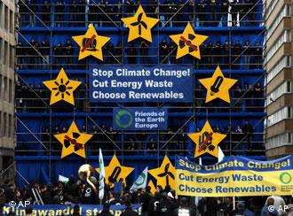 People look at a climate change installation built by Friends of the Earth outside of an EU summit in Brussels. Golden stars on royal blue background symbolising EU flag with message in middle Stop Climate Change