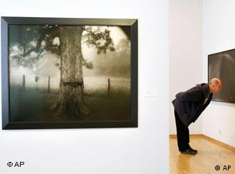 A man looks at a work at a gallery's exhibition