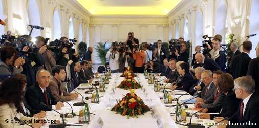 Langer voll besetzter Konferenztisch, außen herum stehen Fotografen und Kameramänner (Quelle: dpa)
