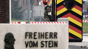 A sign reading Freiherr von Stein Kaserne in front of a guard booth in Germany's national colors with a soldier standing in front of it