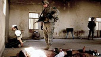 A US soldier guards an wounded arrested man after a gunfight in central Baqouba