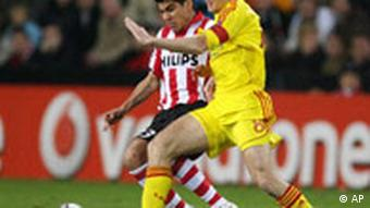 PSV player Carlos Salcido, left, duels for the ball with Liverpool player Steven Gerrard during