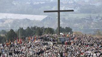 Menschenmenge auf einem Hügel, in der Mitte ragt ein riesiges Kreuz auf (Quelle: dpa)