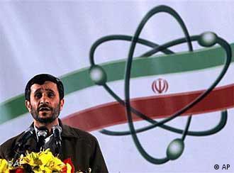 Iranian President Mahmoud Ahmadinejad in front of flag with atomic symbol