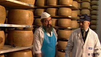 Cheesemaker in front of slabs of parmesan