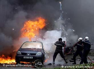 Fire fighters struggle to extinguish a blaze caused by a car bomb in Algeria