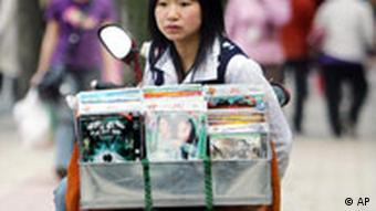 A street vendor sells pirated DVDs and CDs on a motor scooter in Chengdu, China Wednesday, April 11 2007. China reported a sharp monthly drop in its ballooning trade surplus Tuesday and angrily rejected two U.S. complaints filed with the WTO over product piracy and market access for American movies, music and books. (AP Photo/Color China Photo) ** CHINA OUT **