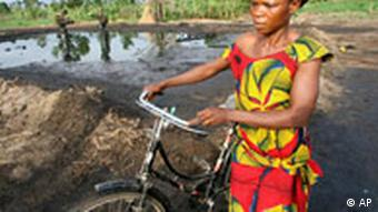 A Nigerian woman with a bicycle. In the background a leaking oil well