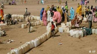Frauen in einem Flüchtlingscamp stehen neben auf dem Boden aufgereihten Wasserkanistern (Quelle: AP)