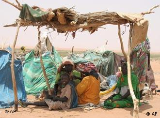 People sitting under a makeshift shelter in the heat