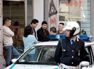 A police officer patrols the streets of the Chinatown district of Milan, Italy, Friday, April 13, 2007, the day after about a dozen police officers and several Chinese immigrants were injured when clashes broke out following a spontaneous protest against a fine, given to a Chinese woman for double-parking and unloading commercial merchandise from a private car in violation of the law. Limin Zhang, the Chinese consul in Milan, said that for the past two months, police have been cracking down on Chinese businesses, particularly concerning the unloading of merchandise. ''The business owners can't do their business,'' he told RAI state television. (AP Photo/Luca Bruno)