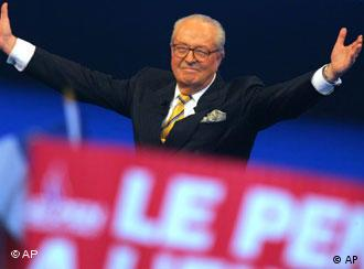 French far-right leader Jean-Marie Le Pen motions while a sign with his name can be seen in the foreground