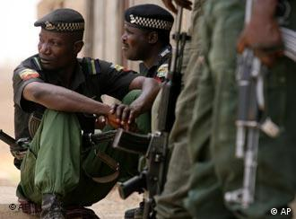 Nigerian police officers stand guard in an area were the military are battling with gunmen in Kano, northern Nigeria