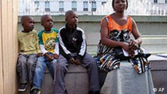 An African family waits outside Paris City Hall during a gathering of illegal immigrants
