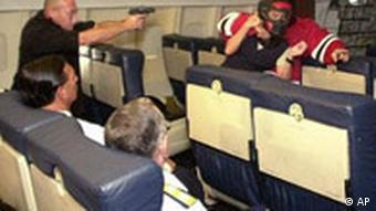 A US air marshal points a gun at a potential terrorist during a mock action