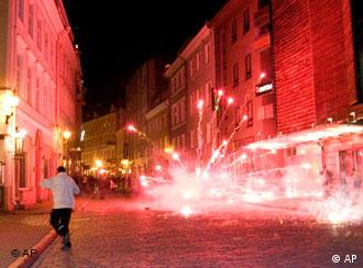 A man runs by exploding flares launched by rebels on a street of central Tallinn during the second night of riots in Estonia.