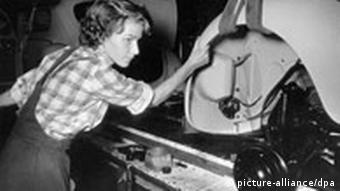A woman working in a Volkswagen factory in the 1950s