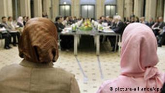 Two women, wearing headscarf, watch members of Germany's Islam conference at tables