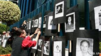 An man hangs photos of slain journalists during a protest at the gates of the Attorney General's Office in Mexico City, Thursday, May 3, 2007.