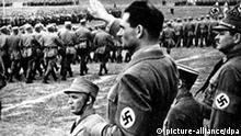 Der Reichsminister und seit 1933 Stellvertreter Hitlers, Rudolf Heß, beim Vorbeimarsch der ostpreußischen SA auf dem Gauparteitag 1934 in Königsberg. 1939 wurde er nach Hermann Göring zu Hitlers 2. Nachfolger ernannt. Um Großbritannien zu Friedensverhandlungen zu bewegen, sprang er am 10. Mai 1941 mit einem Fallschirm über Schottland ab. Die Briten internierten ihn bis Kriegsende. 1946 in Nürnberg zu lebenslanger Haft verurteilt. Rudolf Heß wurde am 26. April 1894 in Alexandria (Ägypten) geboren und hat sich, als einziger Insasse des Kriegsverbrechergefängnisses Berlin-Spandau, am 17. August 1987 in seiner Zelle erhängt.