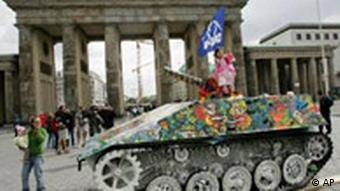 A girl stands on top of a painted 'Peace-Tank' in front of the Brandenburg Gate in Berlin on Tuesday, May 8, 2007. The painted tank is supposed to commemorate the 62nd anniversary of the capitulation of Hitler's Nazi Germany on May 8, 1945 and is also aimed at protesting against the further deployment of German troops in Afghanistan