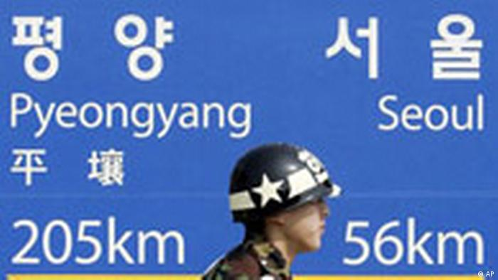 A South Korean military police walks past in front of signboard showing the distance to the North Korean capital Pyongyang and South Korean capital Seoul from Dorasan Station, the last stop in South Korea on a rail link, in the demilitarized zone that separates the two Koreas since the Korean War, in Paju, north of Seoul, South Korea, Thursday, March 15, 2007. Talks between North and South Korea on details of an agreement to conduct test-runs of railways across their heavily armed border ended inconclusively Thursday, the South's Unification Ministry said. (AP Photo/Lee Jin-man)