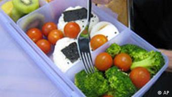 Ein Mann pickt am Mittwoch, 9. Mai 2007, in Frankfurt waehrend der Mittagspause Brokkoli aus seiner mit Reis, Ei, Obst und Gemuese gefuellten Lunch-Box. Mit dem Fuenf-Punkte-Plan Fit statt fett will die Regierung den Trend umkehren, dass immer mehr Deutsche immer dicker werden. Das Kabinett billigte den Plan am Mittwoch. (AP Photo/Ferdinand Ostrop) ----A man picks brokkoli from his lunch box filled with vegetables, fruits, rice and egg during his lunch break in Frankfurt, Germany, Wednesday, May 9, 2007. (AP Photo/Ferdinand Ostrop)