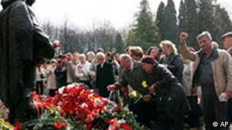People lay flowers at the Bronze Soldier statue at its new location