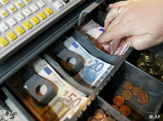 Woman with her hand in a cash register filled with euros