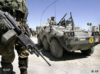 An Italian soldier part of the NATO-forces, left, is seen with his weapon on the outskirts of Kabul