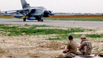 Two German soldiers sit outside eating while a Tornado reconnaissance jet is seen in the background
