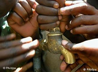 Children hold on to a tap in a village in Malawi